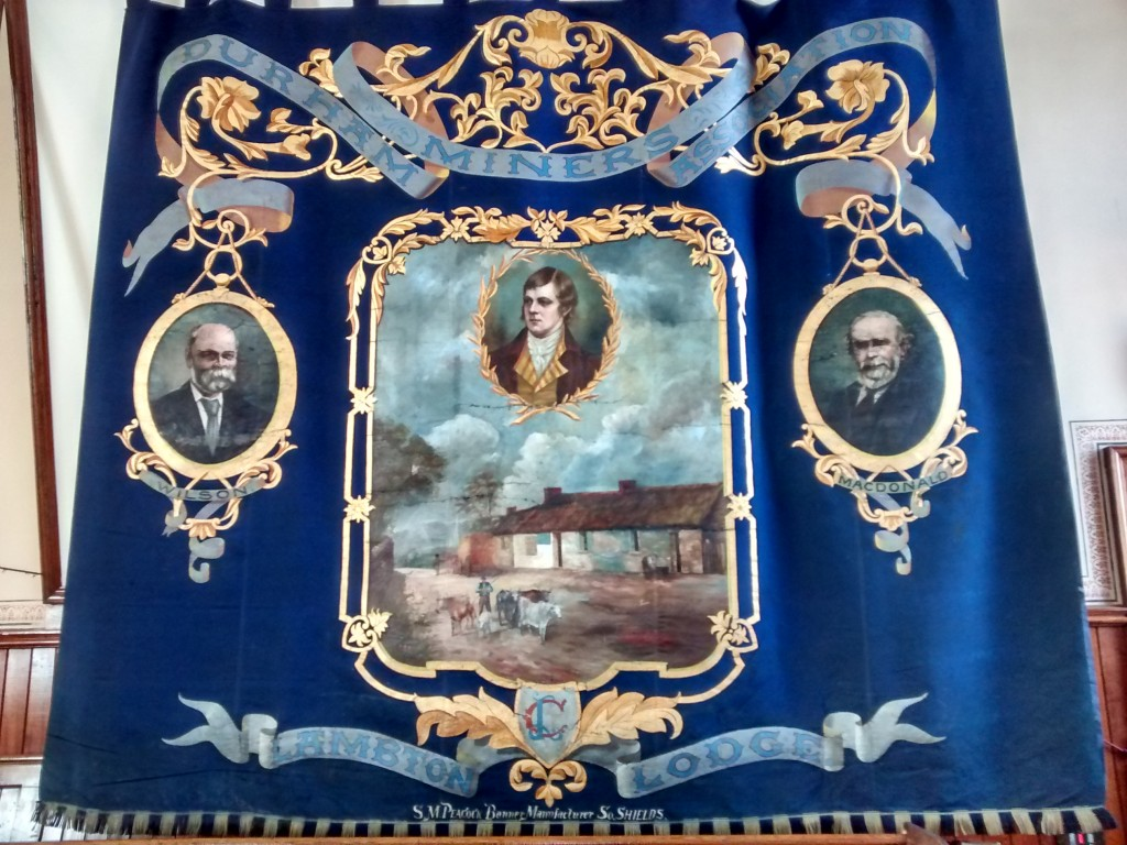 The Lambton banner showing Robert burns, in the central panel, and his birth place.